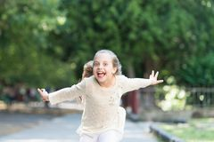 Girl on happy smiling face, nature on background. Child happy and cheerful enjoy walk in park. Happiness concept. Kid royalty free stock images