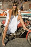 A girl in the harbor with a motocycle. A girl wearing a fashion white dress with a motocycle Royalty Free Stock Photo