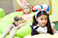 Girl with hare ears hugging Easter bunny stock image