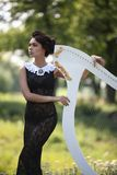 Girl with a harp. Girl in black dress playing the harp white stock photo