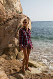 Girl with harpoon in flannel shirt on the rocky beach Stock Photography