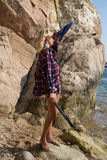 Girl with harpoon in flannel shirt on the rocky beach Royalty Free Stock Photography