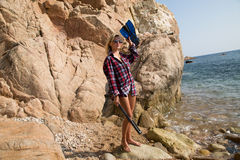 Girl with harpoon in flannel shirt on the rocky beach Stock Photos