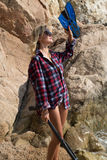 Girl with harpoon in flannel shirt on the rocky beach Royalty Free Stock Photo