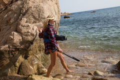 Girl with harpoon in flannel shirt on the rocky beach Royalty Free Stock Photos