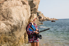 Girl with harpoon in flannel shirt on the rocky beach Royalty Free Stock Image