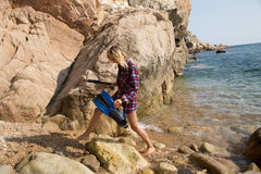 Girl with harpoon in flannel shirt on the rocky beach Royalty Free Stock Images