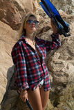 Girl with harpoon in flannel shirt on the rocky beach Stock Image