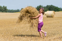 Girl harvesting straw Stock Photography