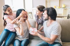 Girl has closed eyes of her mom with hands nad look at her. Dad holds present. He and his son look at young woman. They. Are excited Royalty Free Stock Images