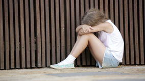 The girl has depression outdoors in the Park. Girl in elementary school age looking depressed outdoors in park stock video footage