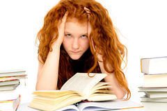 Girl has difficult studies. Red haired girl has difficult studies Royalty Free Stock Photography