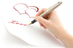 The girl has drawn 2 hearts and writes about love Stock Images