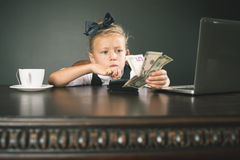 Girl has earned a lot of money. Uses internet by laptop. Banker holds in hand American dollars. Smart business female Stock Photography