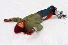 Girl has fun lying in the snow Stock Image