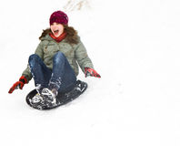 Girl has fun by sledging down the snowy hill Stock Photography