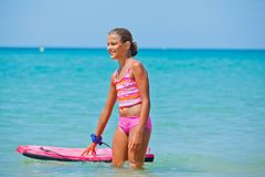 Girl has fun with the surfboard Royalty Free Stock Photo