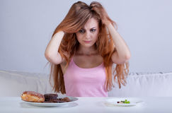 Girl has had enough diet. Near table stock photos