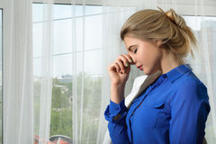 Girl has a headache from fatigue. She is wearing a smart white suit and blue shirt. Concept: office, work, fashion Stock Photo