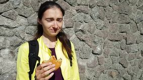 The girl has the hiccups while eating. Funny emotions. A quick snack with a hamburger bun on the street. Dried meat