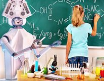 Girl has interactive online learning chemistry and biology course. School child and ai android robot writting on blackboard in classroom. Girl has interactive stock photos