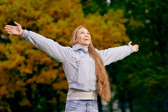 Girl has lifted hands. Young woman has stretched hands against gold autumn foliage of trees Stock Images