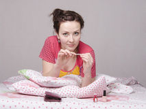 Girl has manicure lying in bed Stock Images