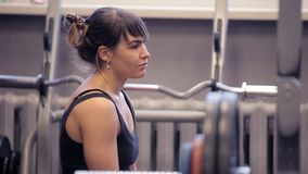 The girl has a rest in the gym. The girl prepares to exercise. the girl is prepared for sports. Raisings of weights. Athletic woman sweating taking a break after stock footage