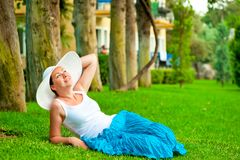 Girl has a rest on a lawn in a hat Royalty Free Stock Photography