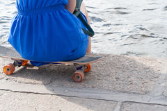 The girl has a rest, sitting on a skateboard Royalty Free Stock Photos