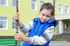 Girl has a rest on a swing at the playground Stock Photography