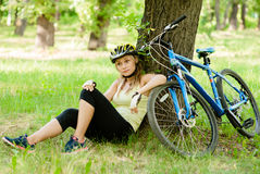 Girl has a rest in the woods after a bike ride Stock Images