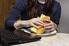 The girl has a sandwich on the workplace behind the laptop stock photo