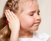 Girl has a sore ear. Child has a sore ear. Little girl suffering from otitis Royalty Free Stock Image
