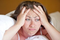 Girl has woken up in the morning in bed in a bad mood Stock Photo