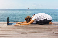 Girl has a yoga practice on the wooden floor with laptop Stock Photo