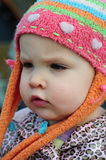 The girl in the hat. A toddler girl with a curious expression wearing a colourful hat Stock Images