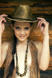 The girl and a hat. �owboy's dress. The girl keeps for hat and smiles. Style the Wild West Royalty Free Stock Photo
