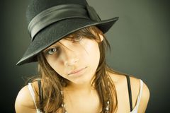 Girl with hat. A teenager girl looks into the camera dressed in a sleeveless top and a black hat with a bow Stock Photography