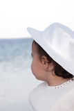 Girl in hat. Little girl wearing hat gazing at the sea royalty free stock image