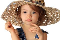 A girl is in a hat. A little girl is in a straw hat Stock Photography