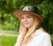Girl in hat against park. Pretty blonde girl in hat against park Royalty Free Stock Images