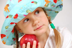 Girl with hat and apple stock image