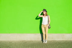 Girl in a hat on a background of green wall. Young beautiful girl in a hat on a background of green wall Royalty Free Stock Images