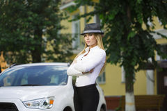 Girl in a hat on a background of white car Stock Photos