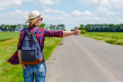 Girl with hat and backpack hitchhiking on the road. Girl with hat and backpack hitchhiking on the rural road royalty free stock images