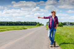 Girl with hat and backpack hitchhiking on the road. Girl with hat and backpack hitchhiking on the rural road royalty free stock photography