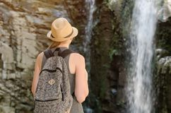 Girl in a hat with backpack looking at a waterfall. View from the back Stock Images