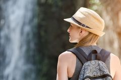 Girl in a hat with backpack looking at a waterfall. View from the back Royalty Free Stock Photo