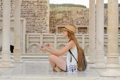 Girl in a hat with a backpack sitting in the lotus position among the marble columns. Journey Royalty Free Stock Photos
